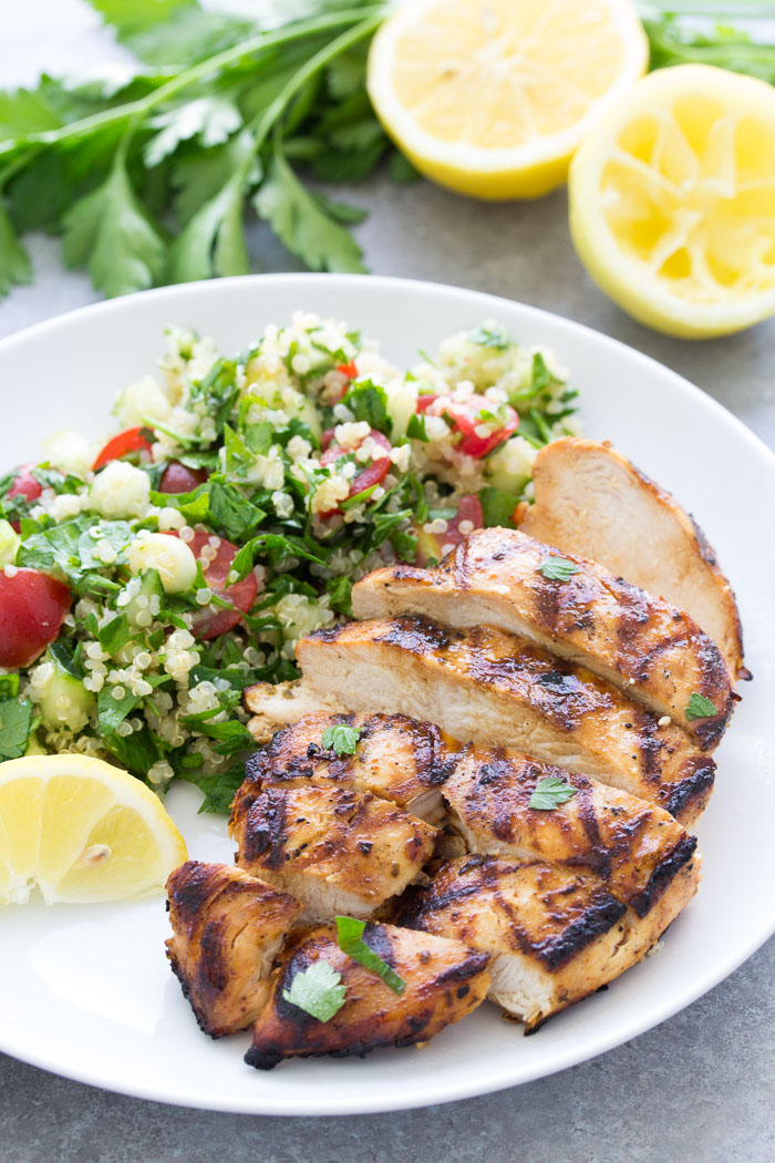 sliced grilled chicken on a plate with side of salad