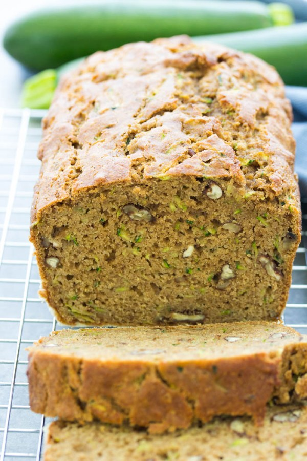 loaf of zucchini bread with slices on a cooling rack