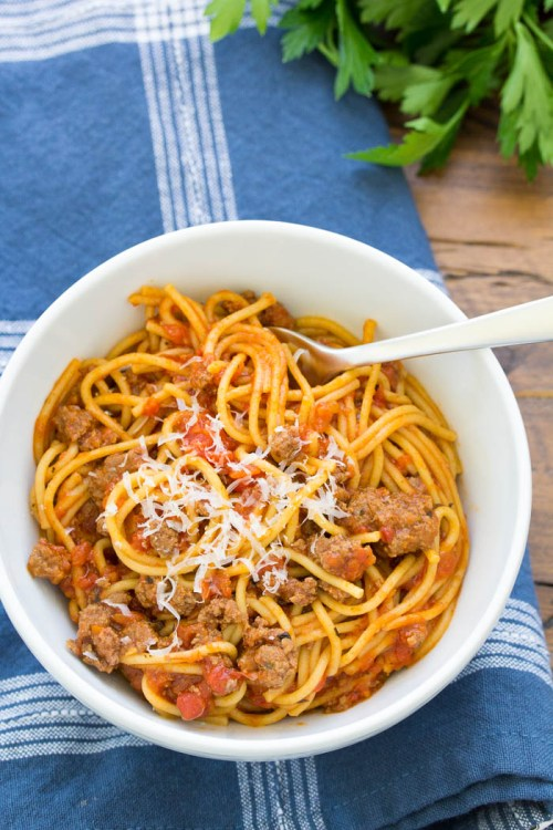 Instant Pot Spaghetti with meat sauce in a bowl, topped with parmesan cheese.
