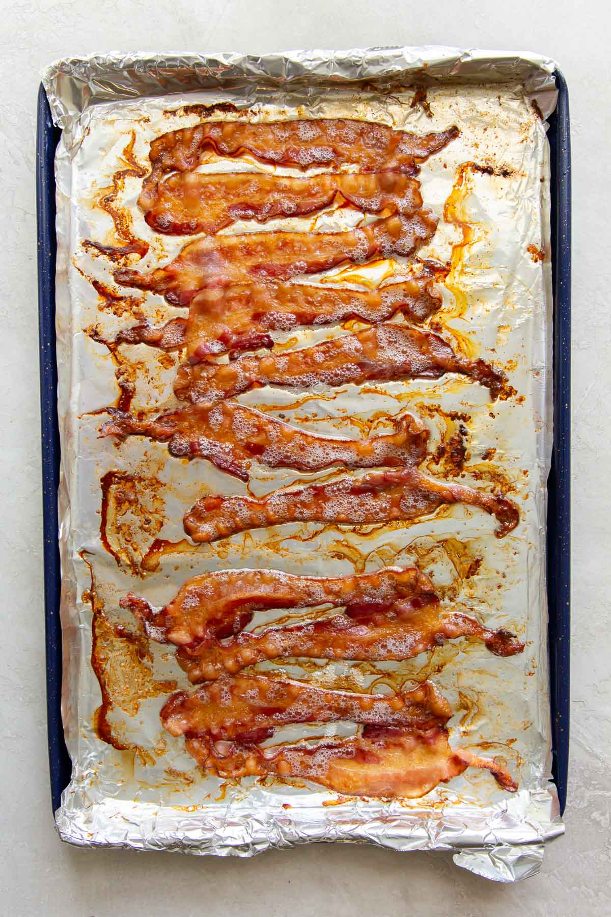 baked bacon slices on a foil-lined rimmed baking sheet