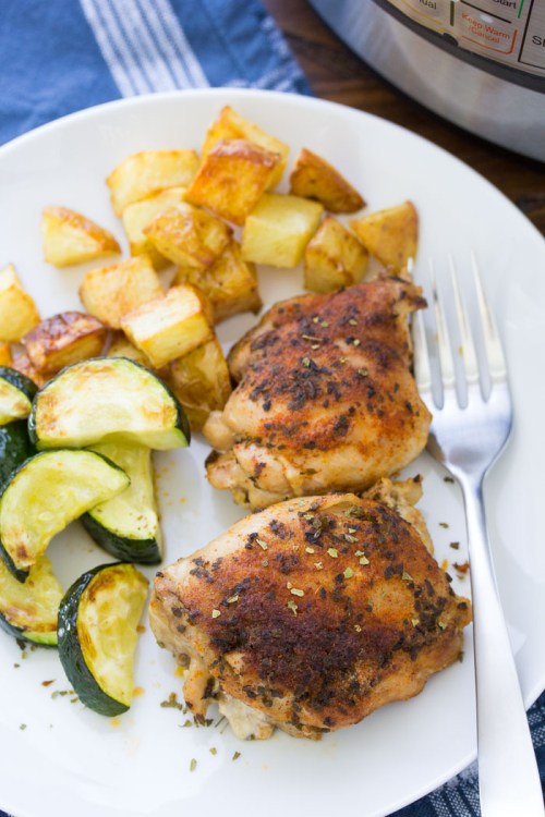 Instant Pot chicken thighs on a plate with potatoes and zucchini.