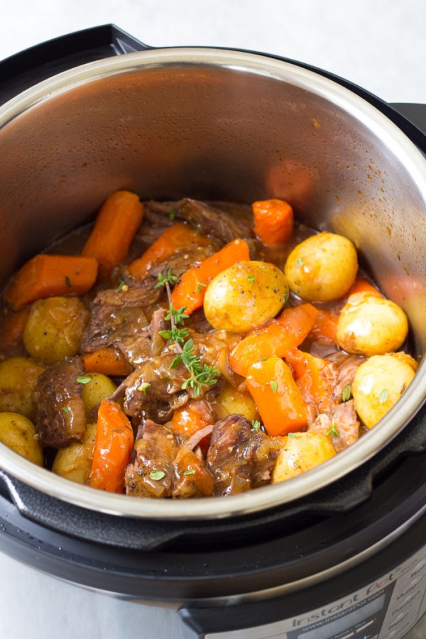 Pressure cooker pot roast with potatoes and carrots in the Instant Pot after cooking.