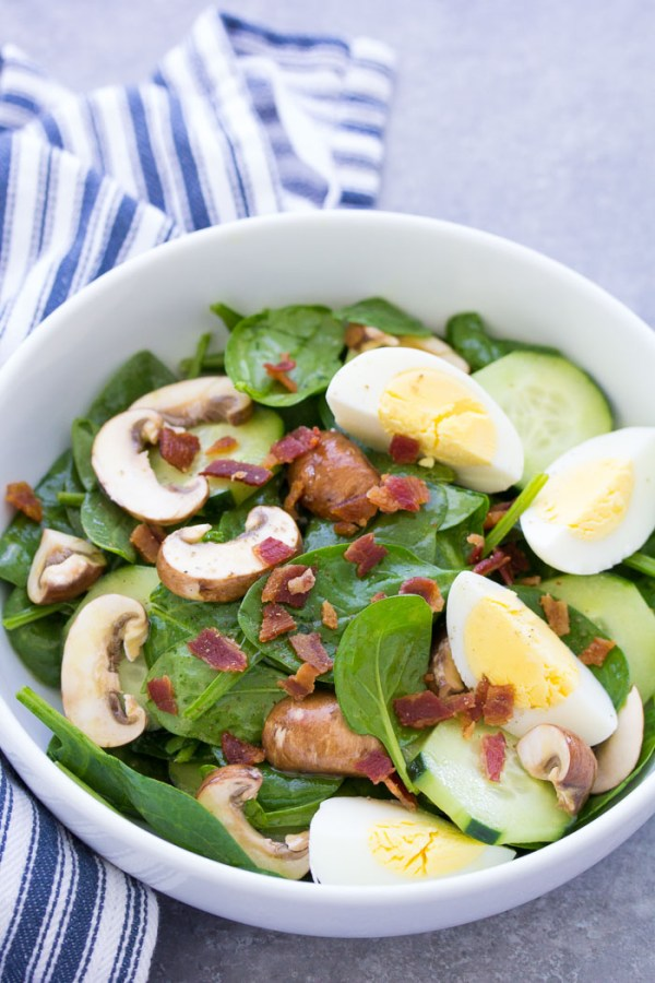 Spinach salad with bacon and eggs in a bowl.