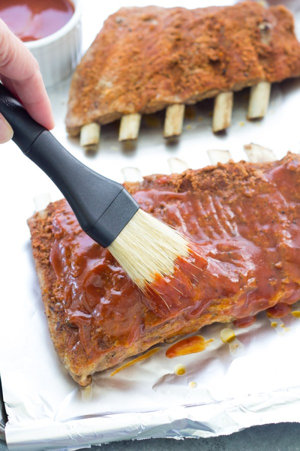 Brushing bbq sauce on pressure cooked ribs to go under the broiler.