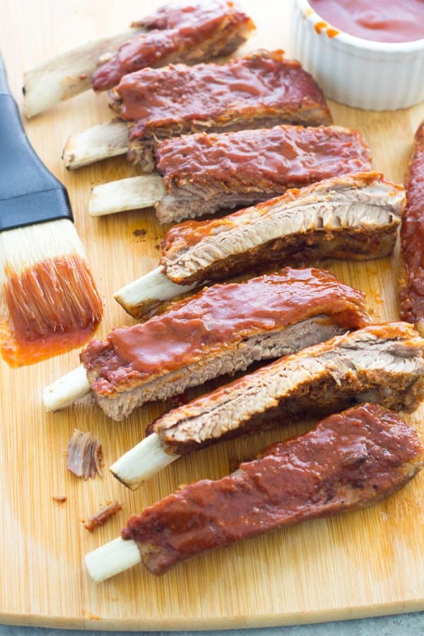 Baby back ribs on a cutting board with barbecue sauce, after cooking in the Instant Pot.
