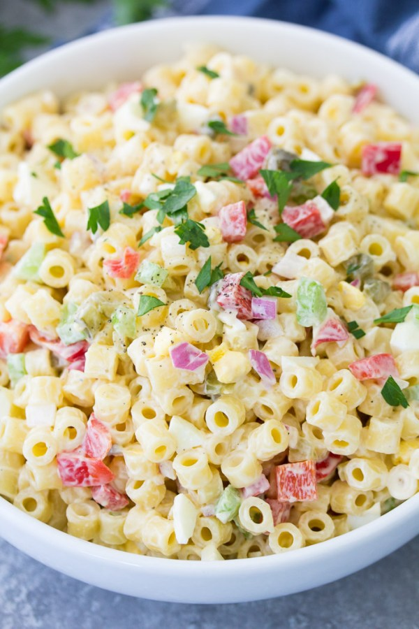 Close up of macaroni salad in a white serving bowl.
