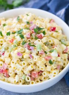 Macaroni salad in a white serving bowl with parsley garnish.