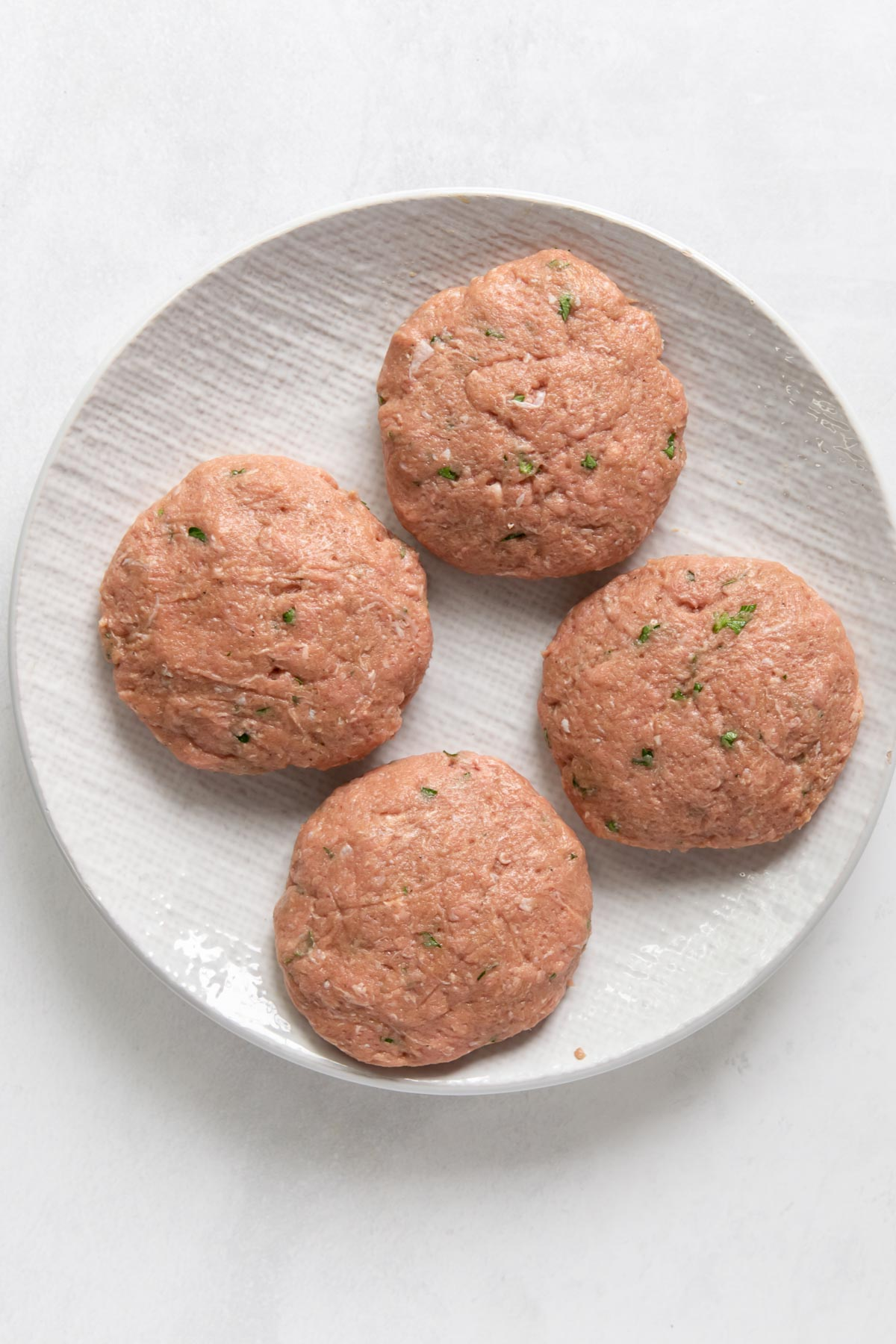 four uncooked turkey burger patties on a plate
