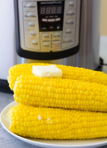 Corn on the cob with butter in front of an Instant Pot.
