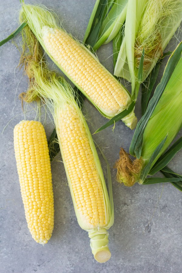 Removing the husks from fresh corn on the cob.
