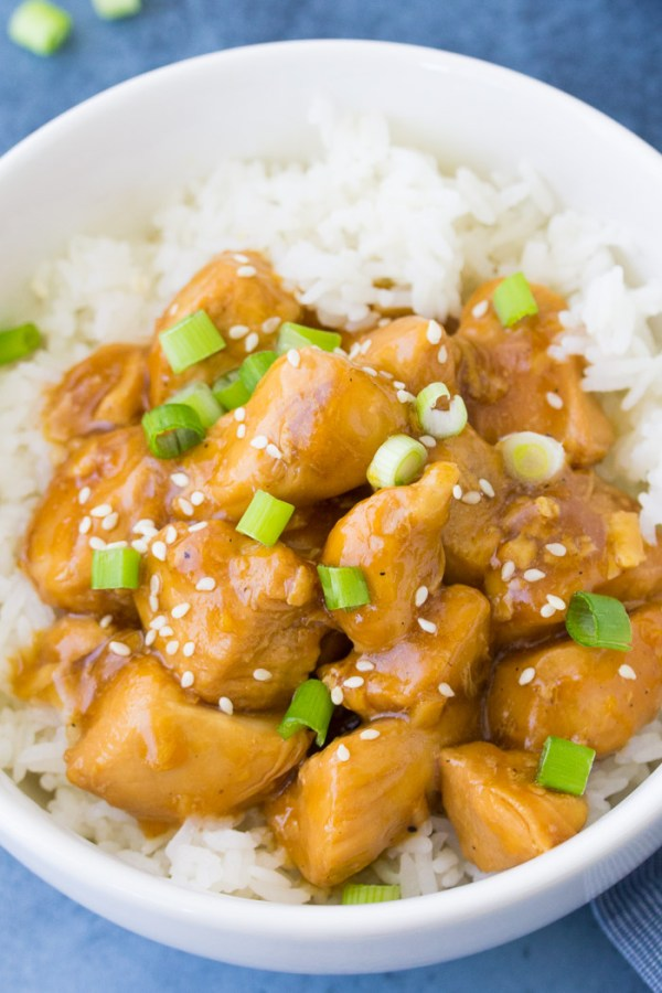 Close up of instant pot orange chicken served in a bowl with white rice.