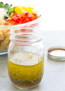 Homemade Italian dressing in a mason jar with pasta salad in the background.