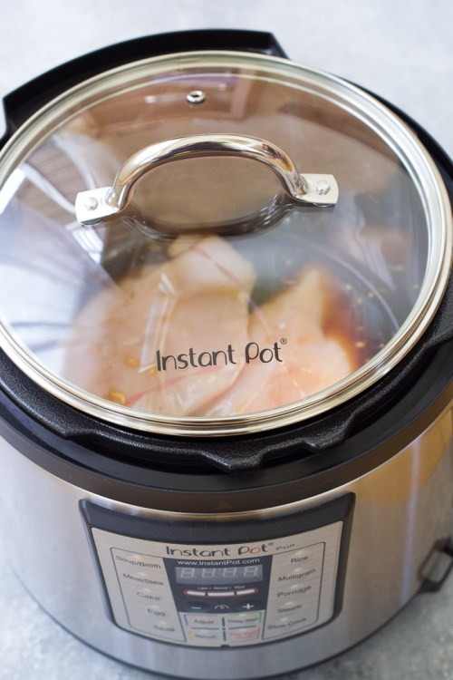 Chicken slow cooking in an Instant Pot with a glass lid.