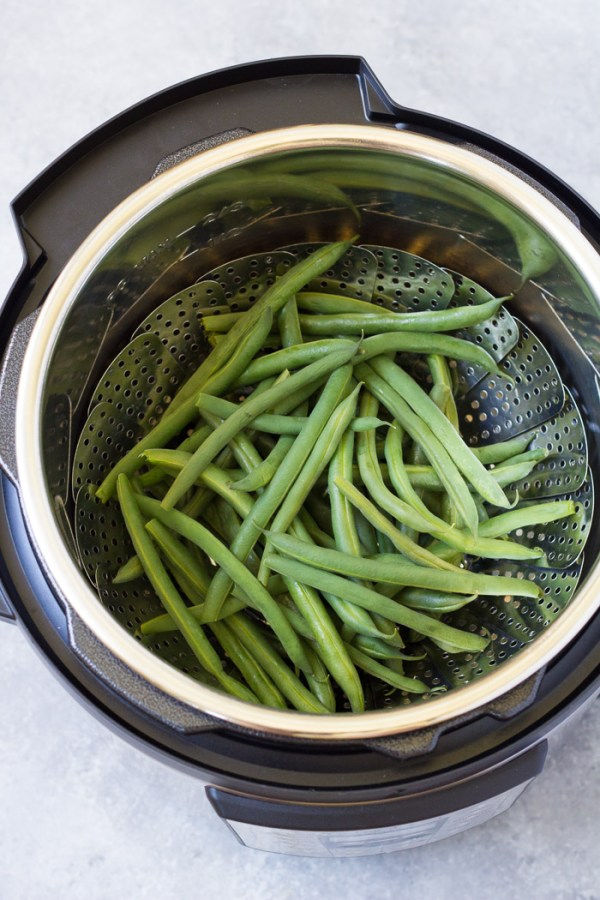Green beans in a steamer basket in an Instant Pot.
