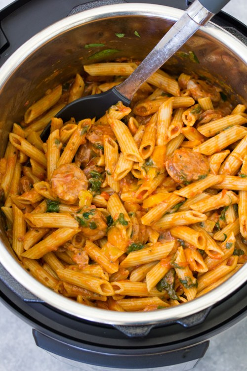 Instant Pot pasta with sausage and veggies in an Instant Pot pressure cooker, with a serving spoon.