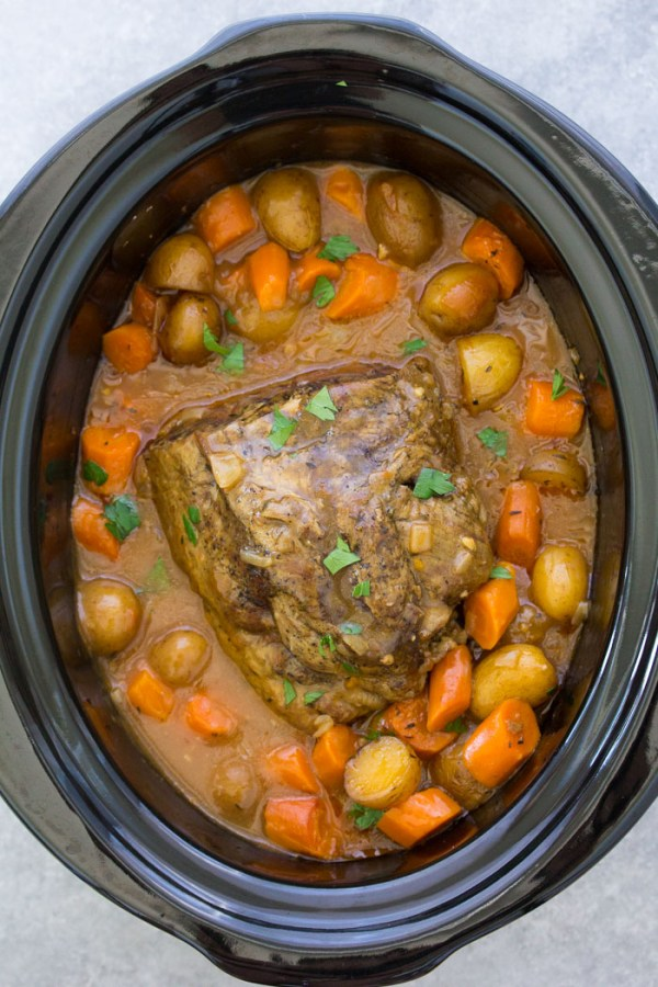 Overhead view of chuck roast in a slow cooker with vegetables and gravy.