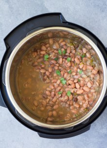 Cooked pinto beans in an Instant Pot pressure cooker, garnished with cilantro.