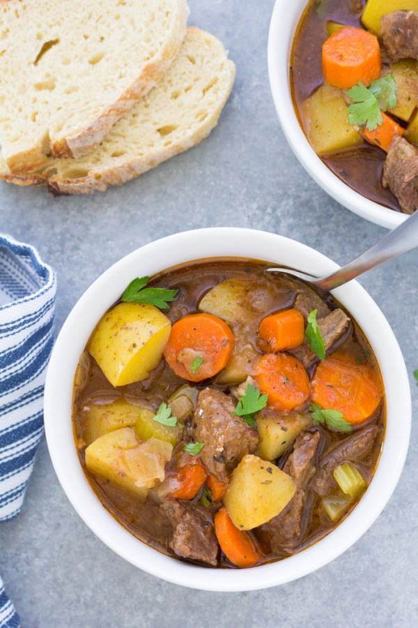 Overhead photo of two bowls of beef stew, with sliced sourdough bread.