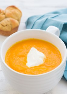 cup of carrot ginger soup with a dollop of sour cream