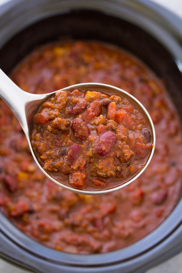 Ground beef chili with beans on a ladle above a slow cooker.