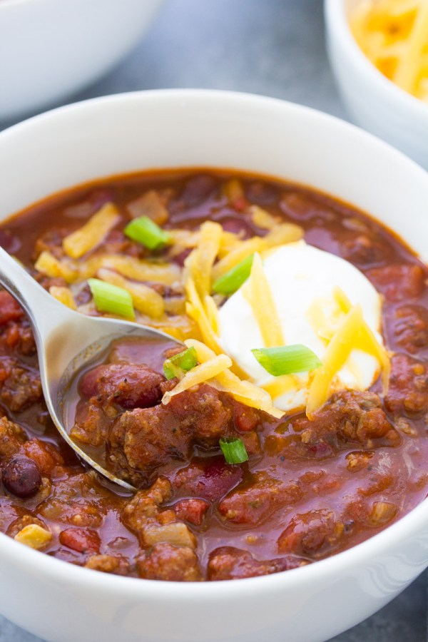 Close up of beef chili being scooped onto a spoon from a bowl.