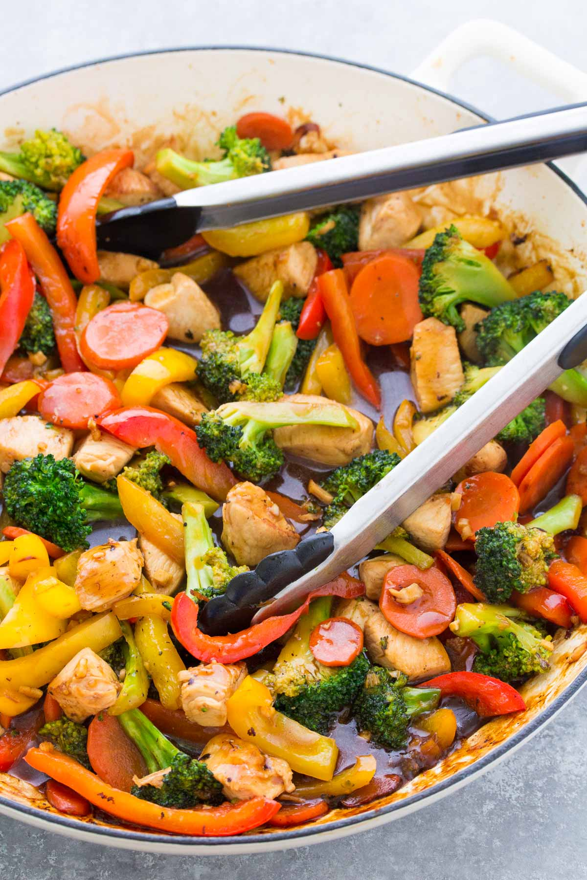 Chicken stir fry with vegetables and sauce in a large skillet.