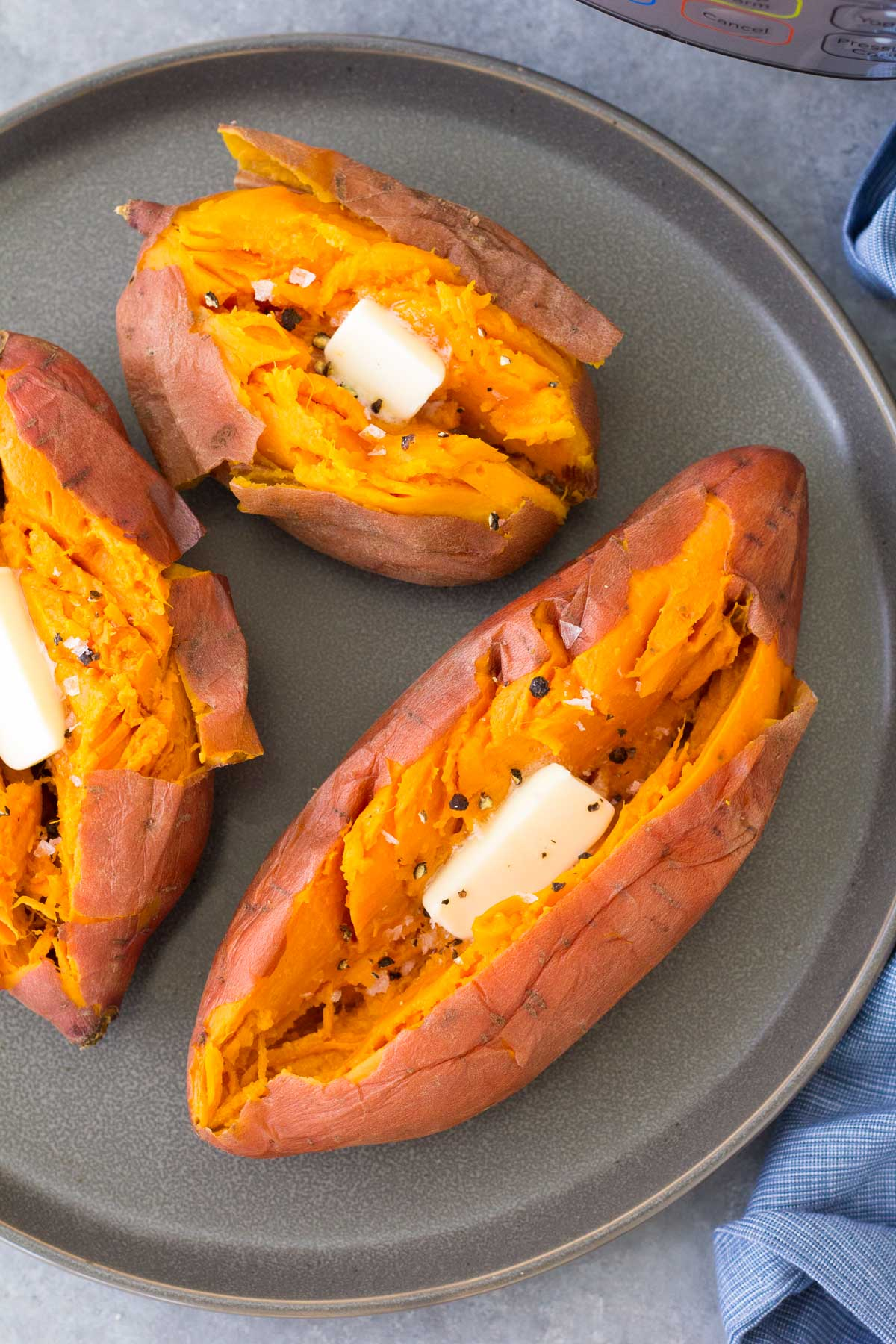 Baked Instant Pot sweet potatoes with butter, salt and pepper on a gray plate.