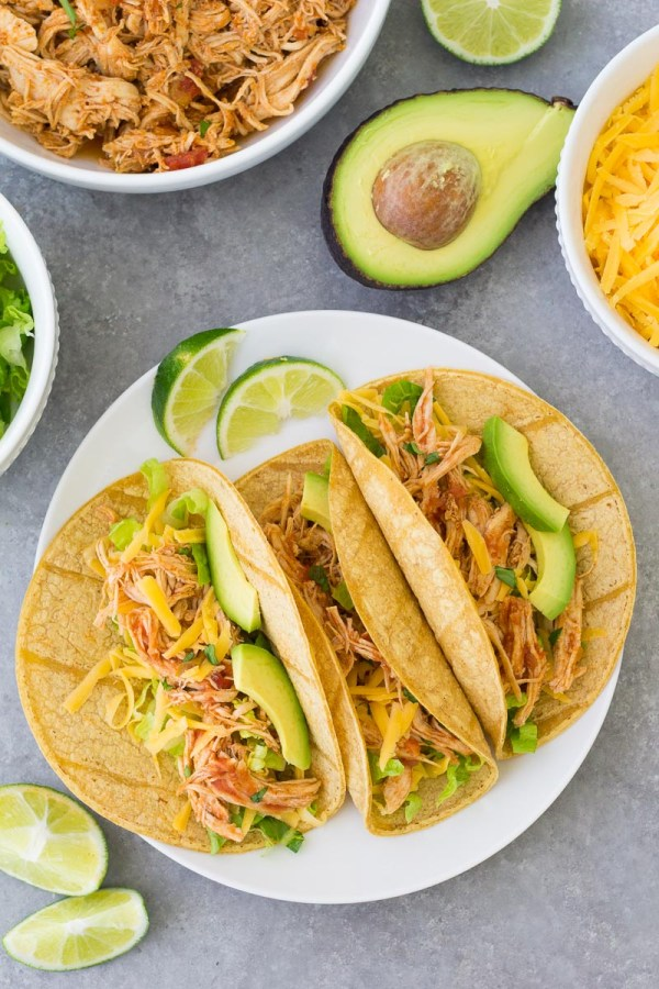 Three chicken tacos on a plate with limes, shredded chicken, lettuce, cheese and avocado on the table.