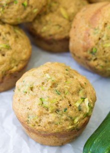 Close up of a zucchini muffin with a pile of muffins in the background and a fresh zucchini on the side.