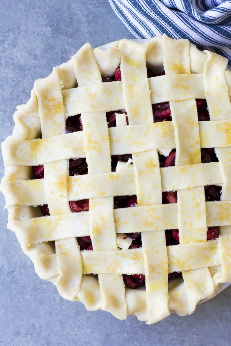 Pie before baking with a woven lattice top crust.