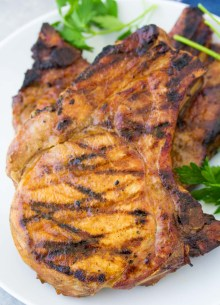 Grilled pork chops on a white plate with parsley.