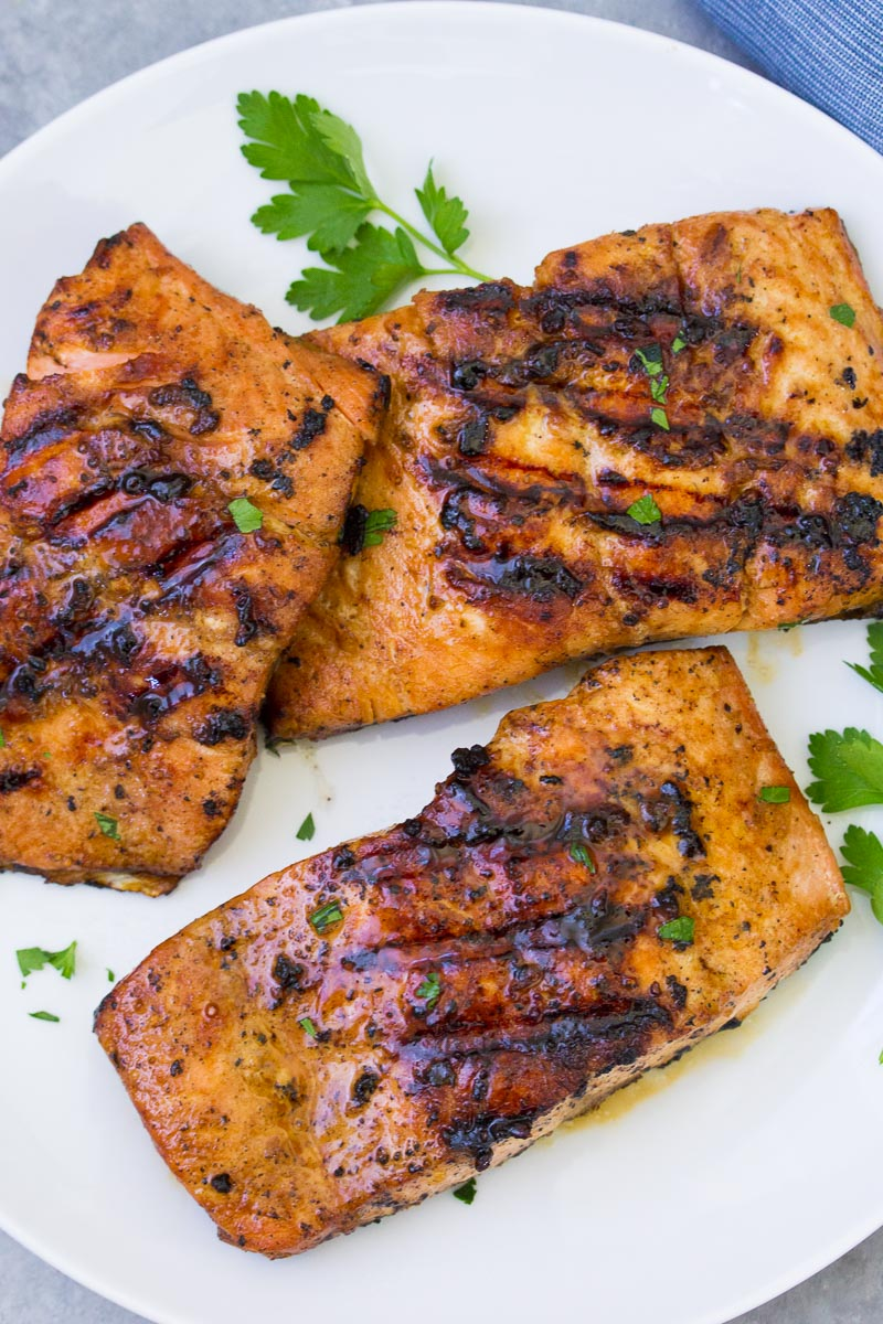 Three grilled salmon fillets on a white plate.