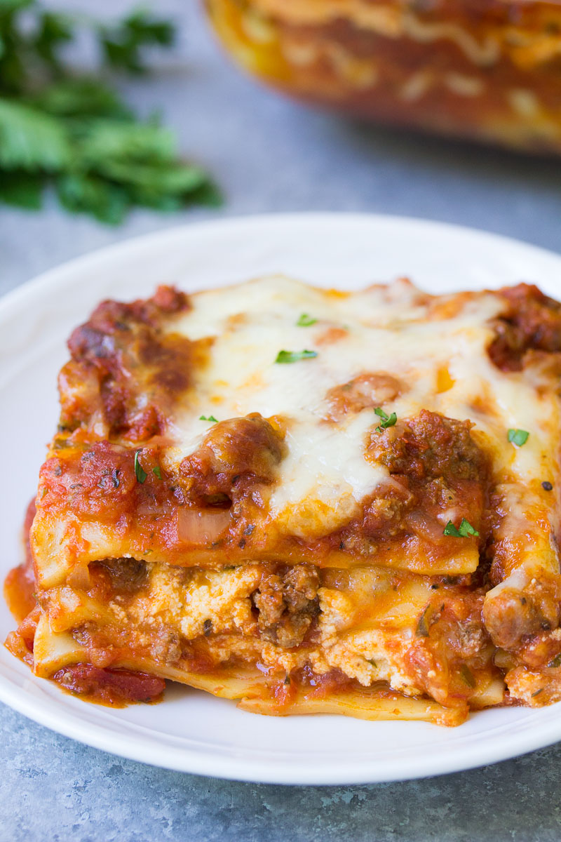 Slice of lasagna on a white plate.