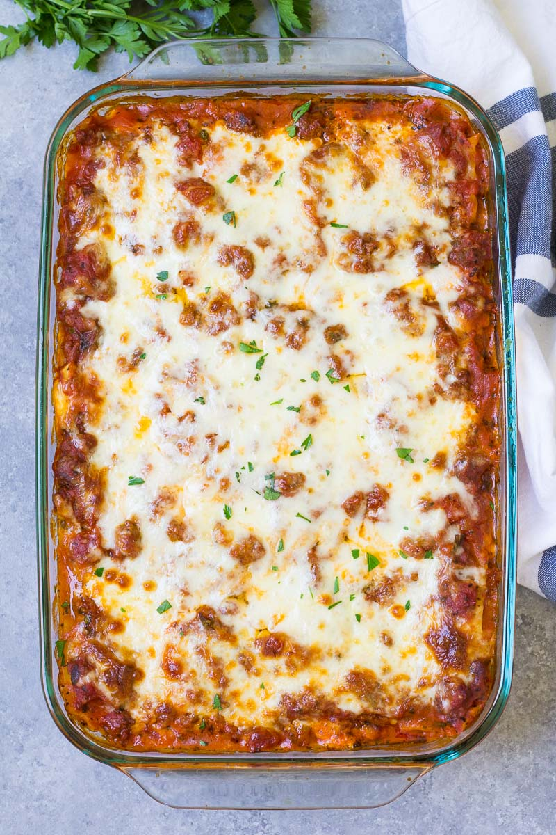Cheesy, saucy lasagna in a baking dish after baking.