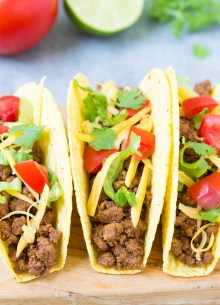 Three beef tacos in crunchy shells with cheese, lettuce and tomato.