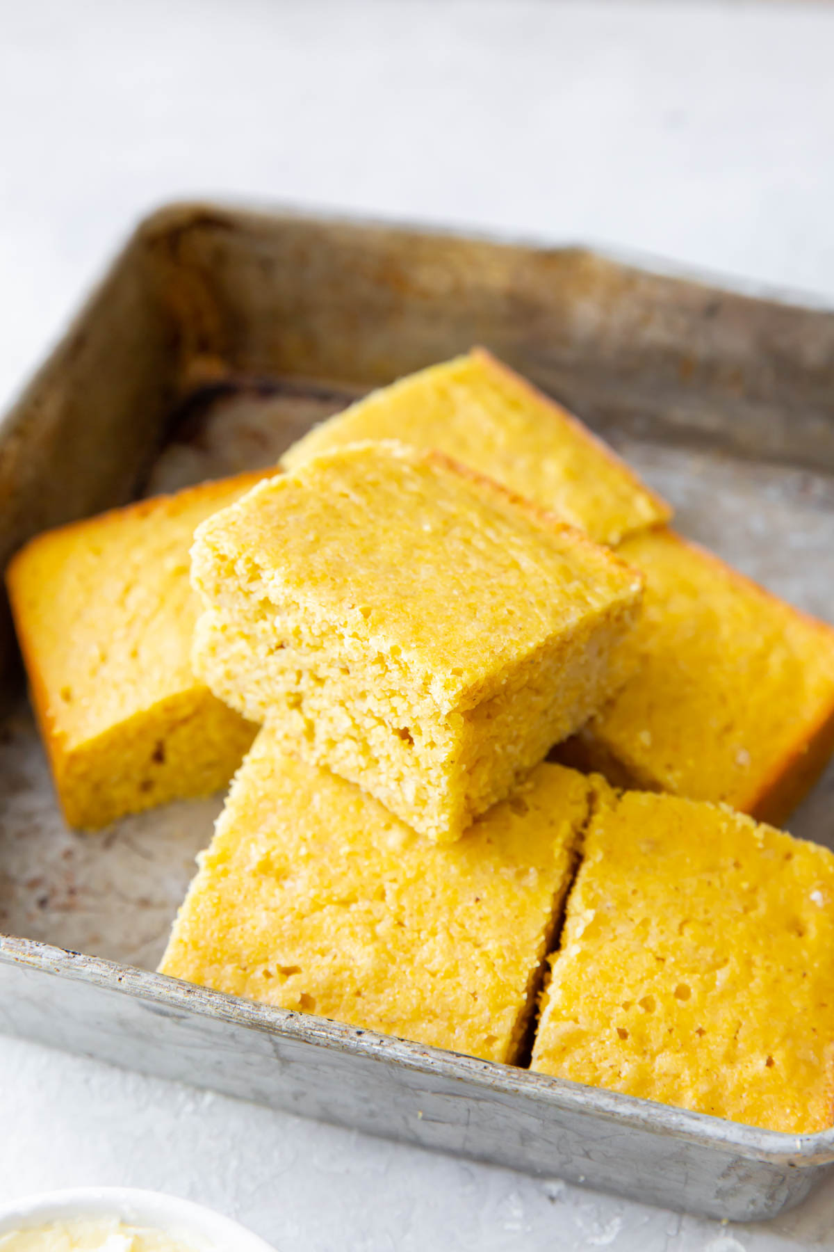 slices of cornbread stacked in baking pan