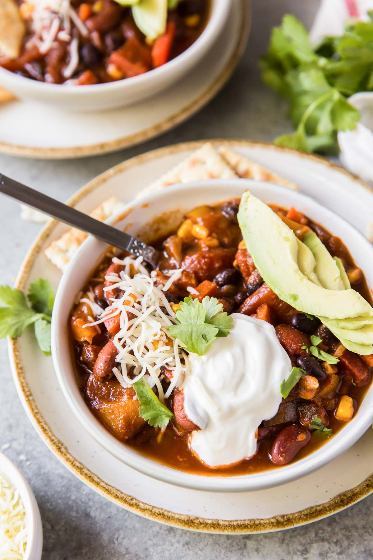 vegetarian chili in a serving bowl topped with sour cream, cheese and avocado