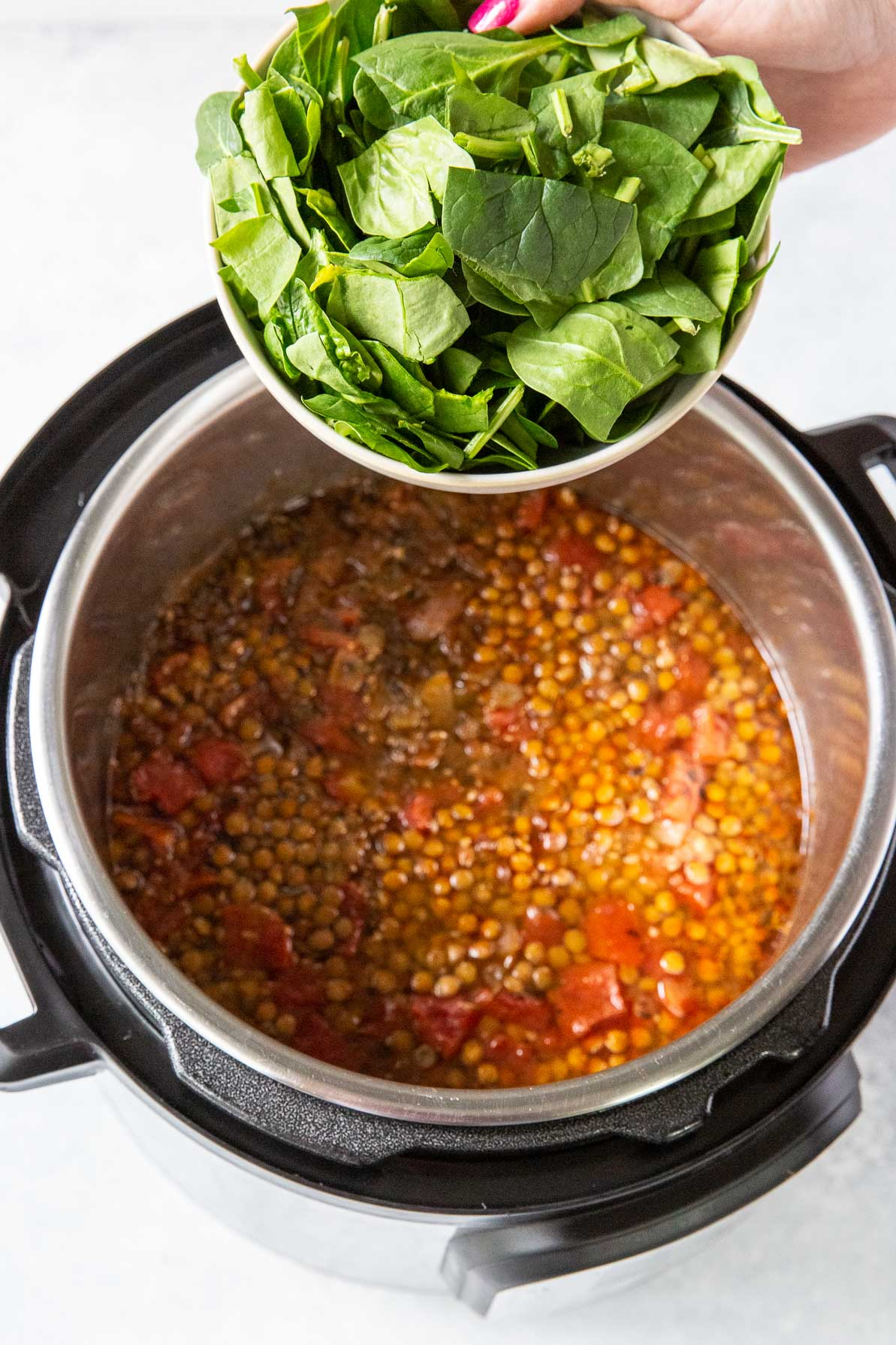 adding spinach to cooked soup
