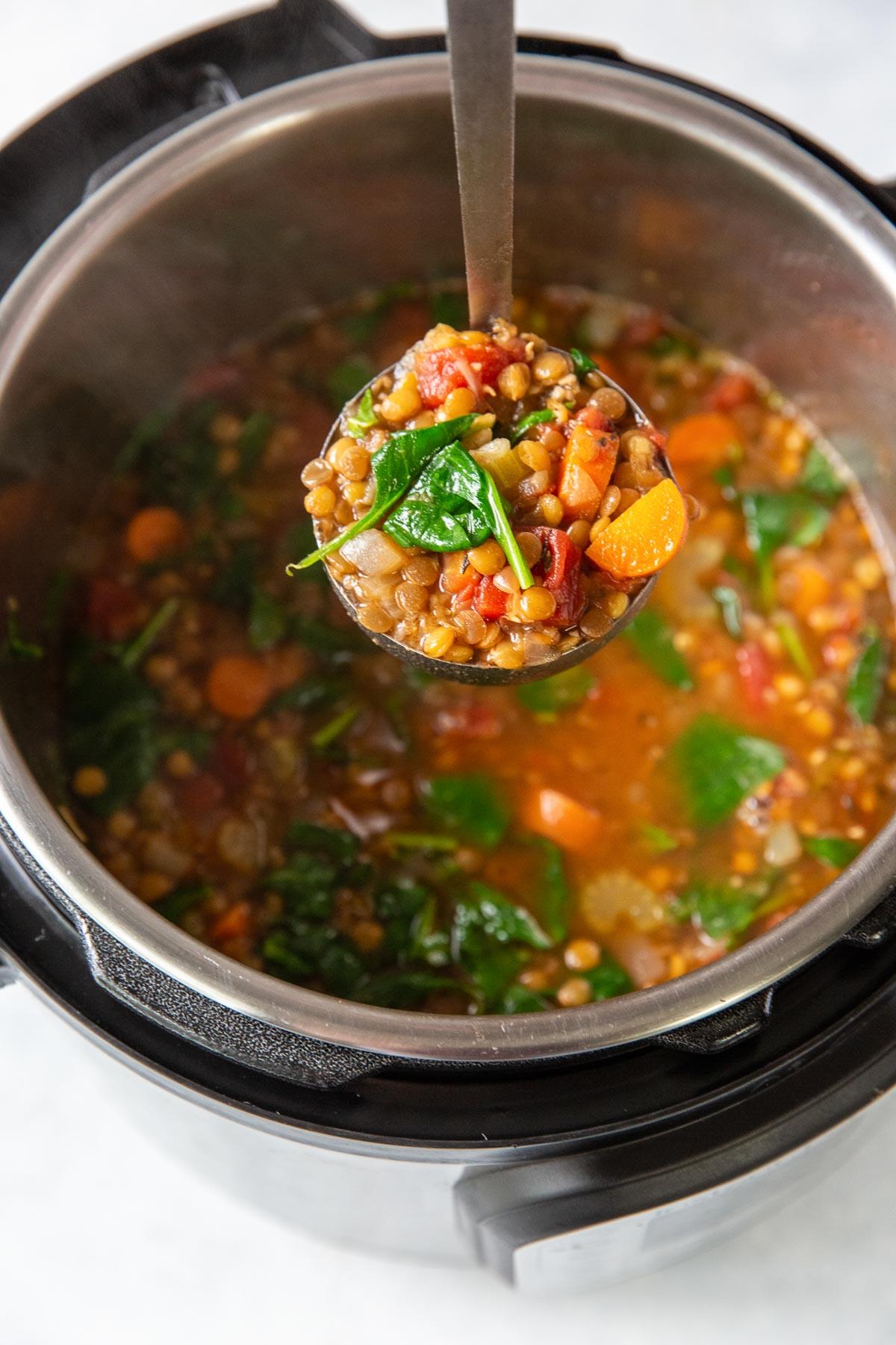 lentil soup on a ladle held over an instant pot