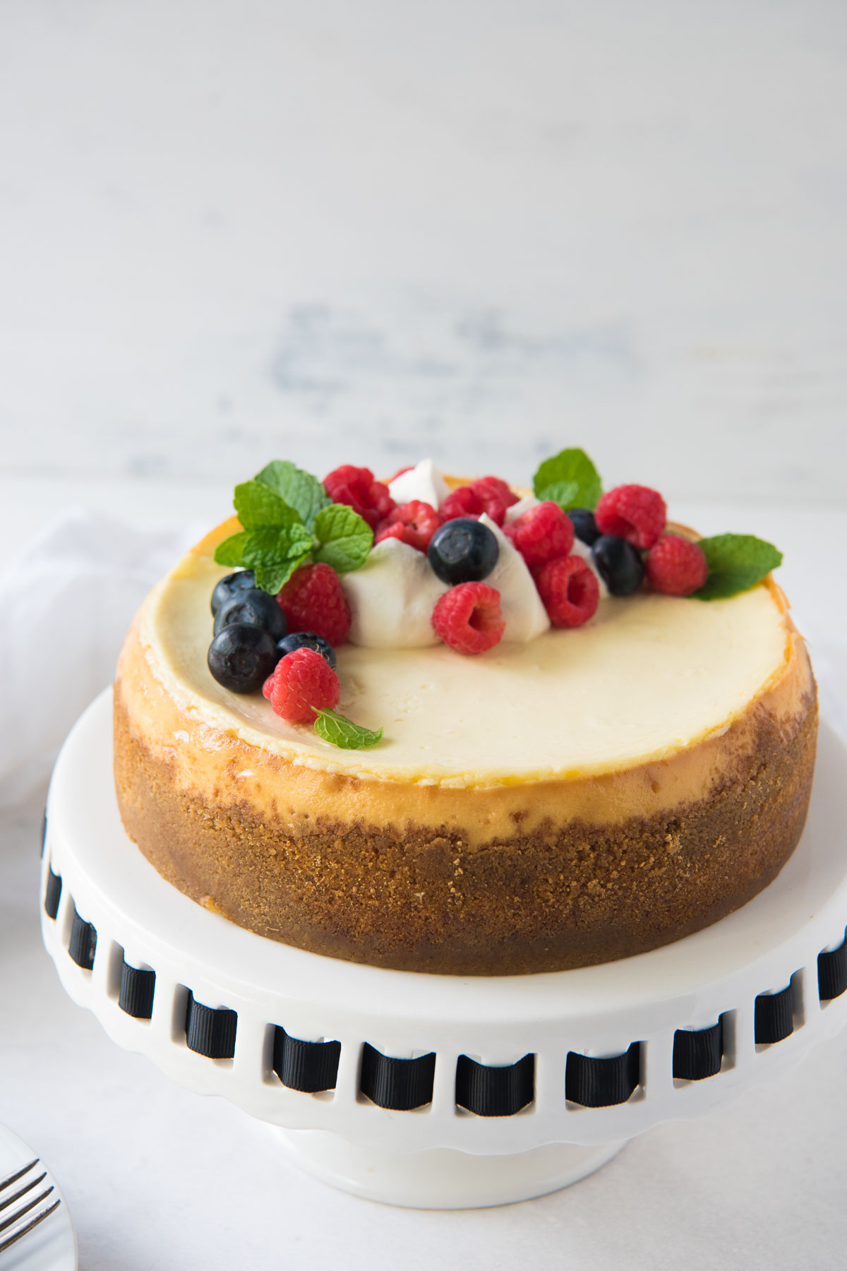 cheesecake topped with whipped cream and fresh berries on a cake stand