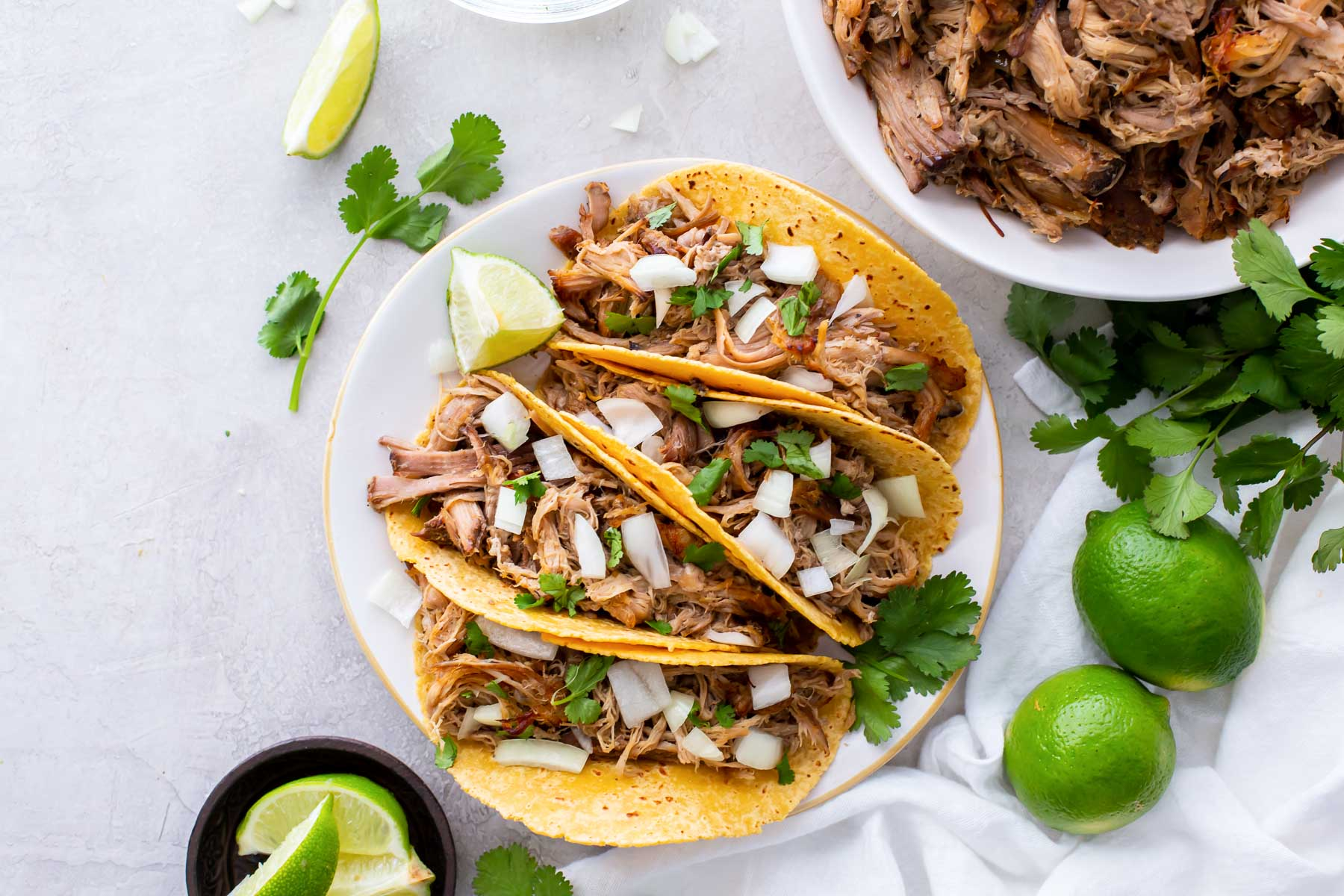 shredded pork tacos on a plate with bowl of carnitas in background