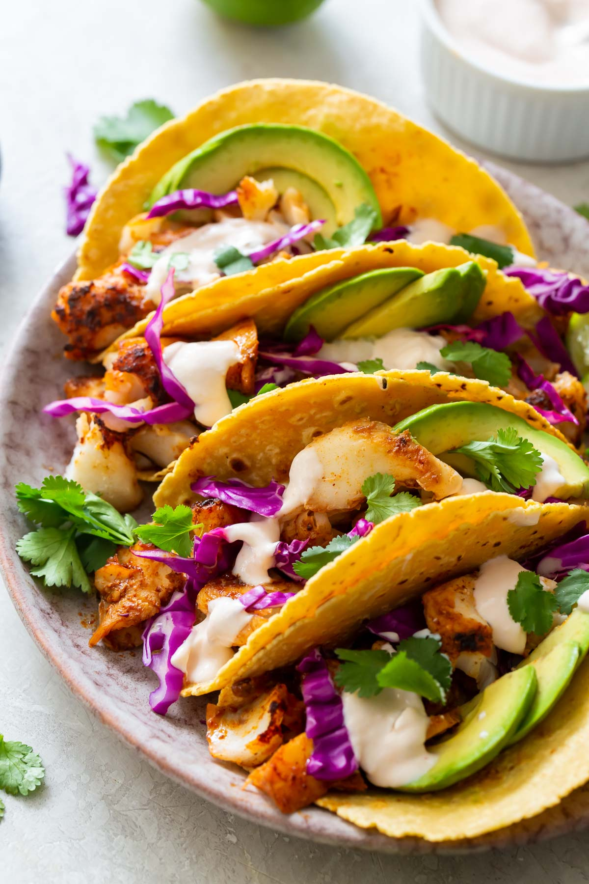 fish tacos assembled on a plate with fish taco sauce in background