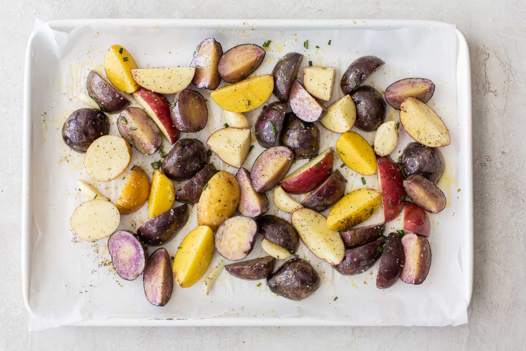 potatoes and garlic cloves tossed with olive oil and seasonings on baking sheet