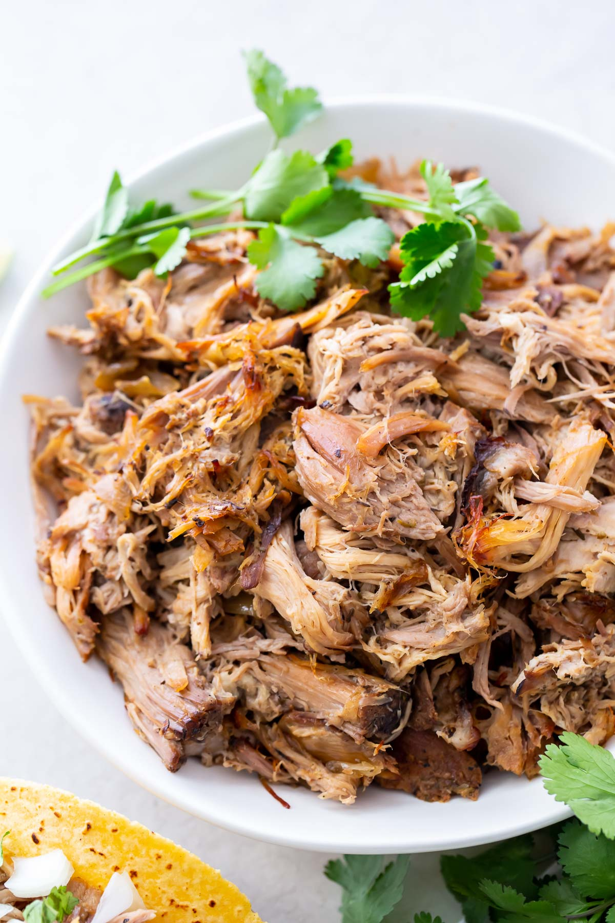 shredded Mexican pulled pork in a bowl, garnished with cilantro