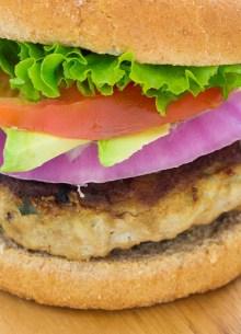 turkey burger on bun with onion, avocado, tomato and lettuce
