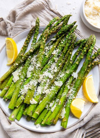 asparagus on a serving plate with lemon and Parmesan cheese