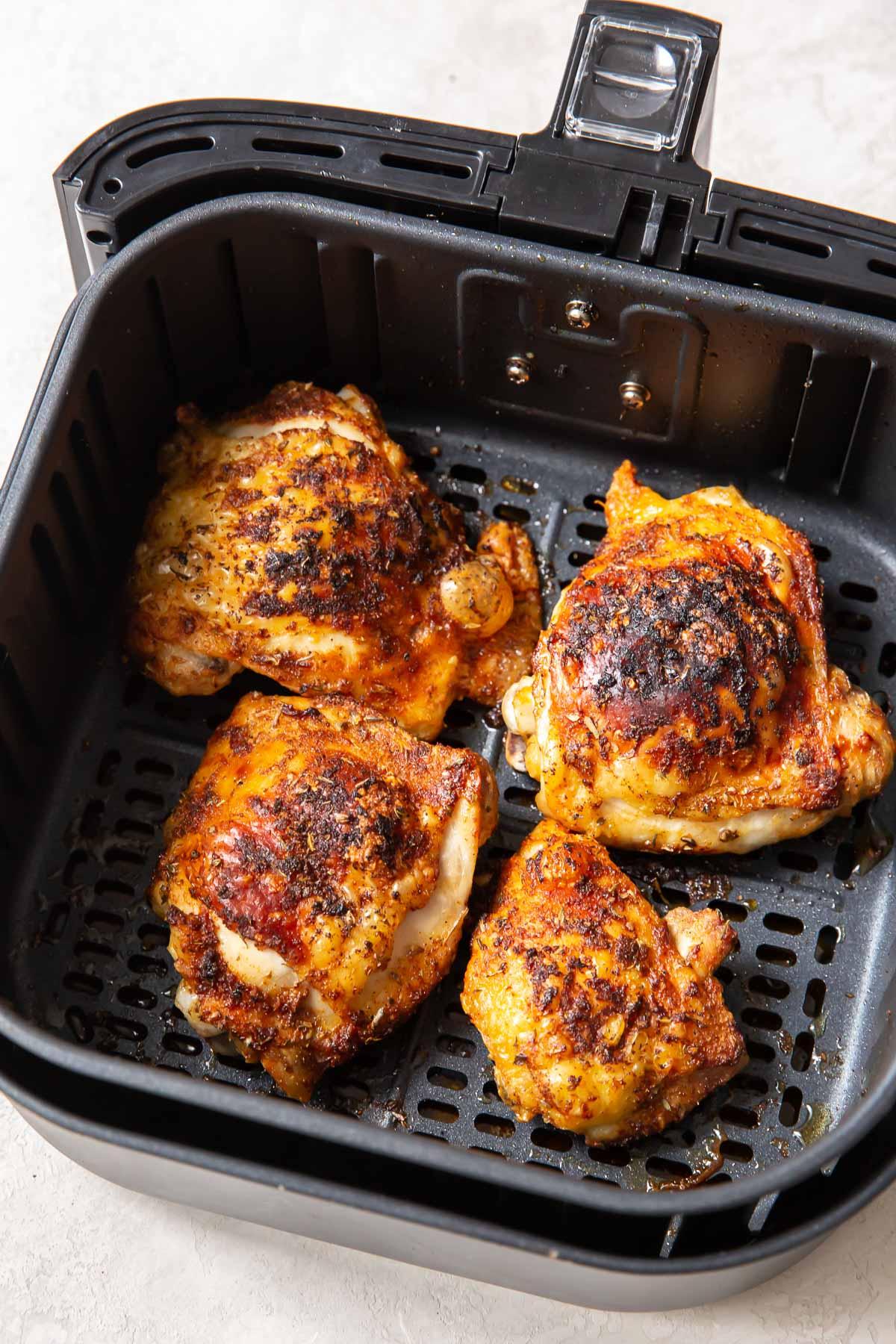 cooked crispy chicken thighs in air fryer basket
