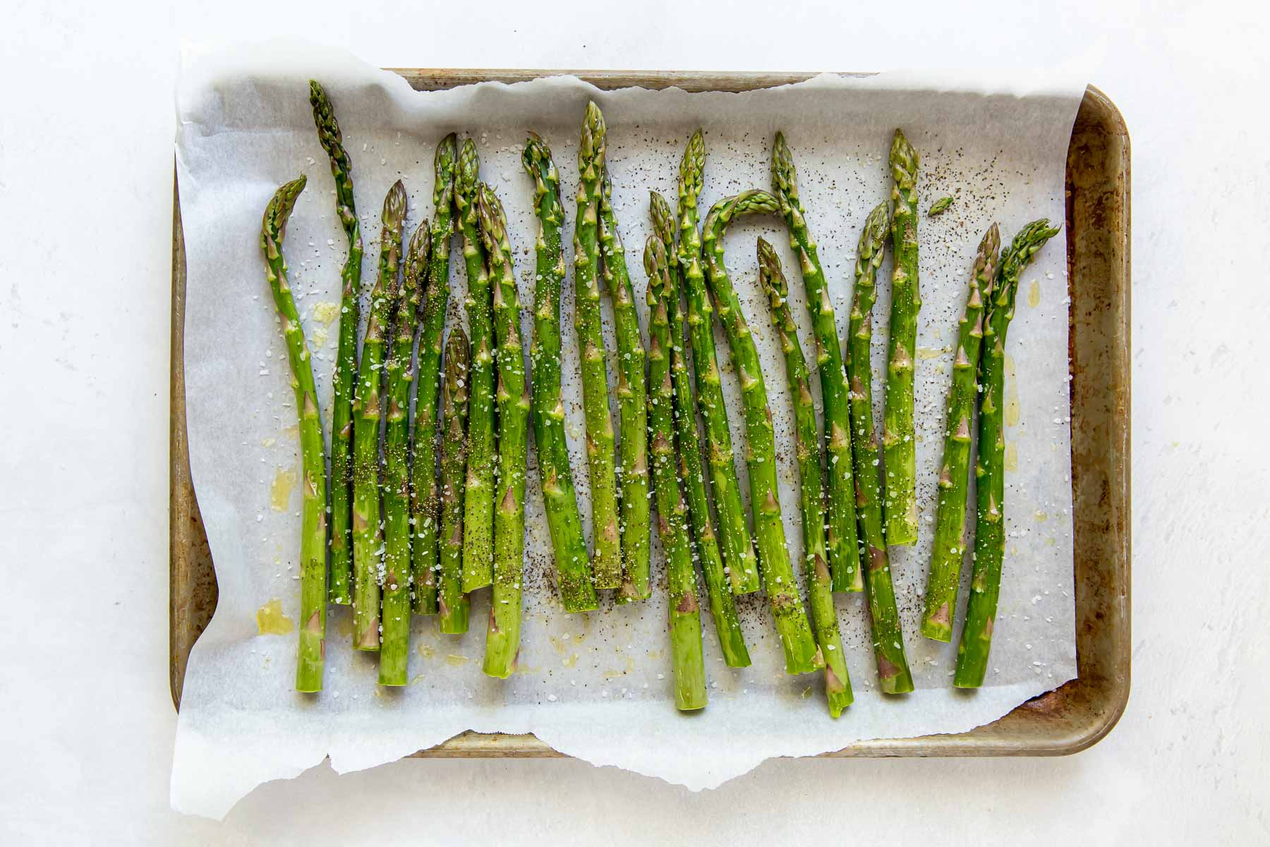 asparagus on baking sheet tossed with olive oil, salt and pepper