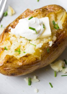 baked potato topped with butter, sour cream and chives
