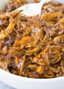 shredded bbq pulled pork in a bowl with two forks
